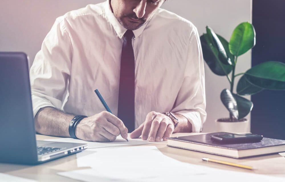 gestor apropriando custos de obra em anotação de papel