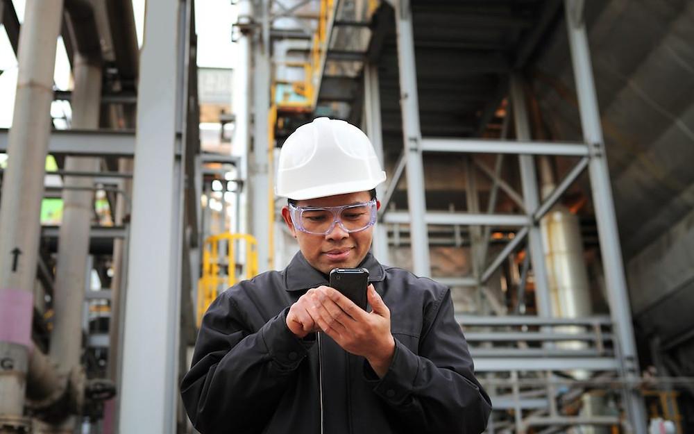 colaborador apontando atividade com celular na fábrica