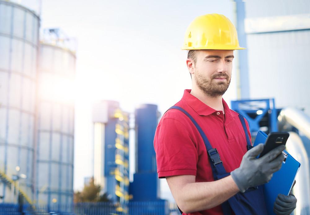 trabalhador, capacete amarelo apontando em um smartphone