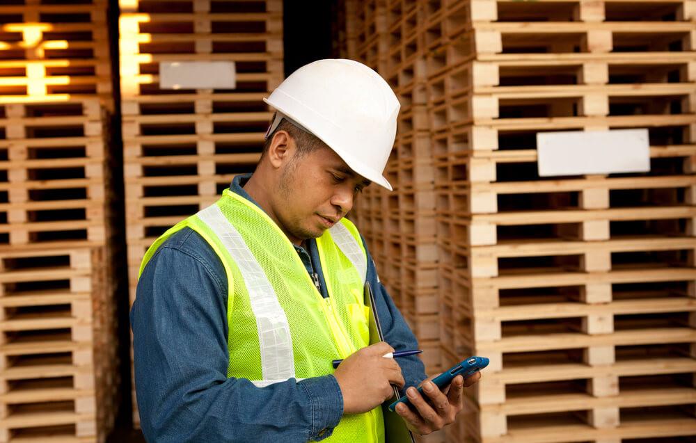 operario fazendo apontamenot eletrônico em seu smartphone, entre palets, com capacete branco e roupa de segurança