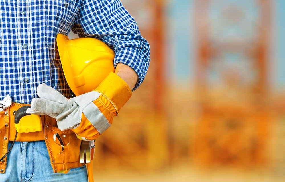 construção civil, operario camisa chadrez com capacete amarelo e luvas na mão, apontando atividades na obra