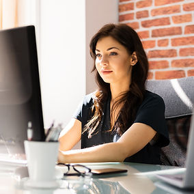 woman-sitting-at-desk-in-front-of-computer