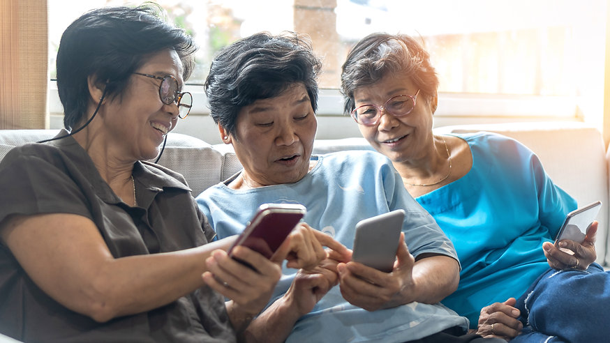 Three older women of Asian heritage sitting on a couch and reading messages on a smart phone