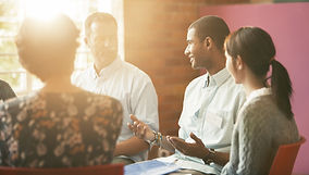 group of coworkers talking in a circle with focus on young black man speaking
