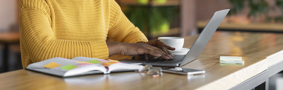 Young black woman in yellow sweater sitting at desk and working on laptop computer