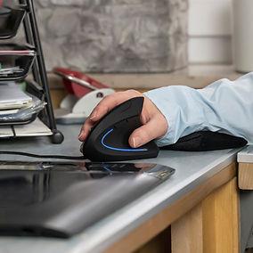 white man in long-sleeve light blue shirt using ergonomic mouse on his desk