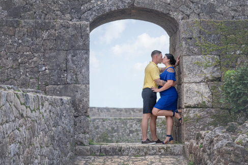 couple kissing under stone archway