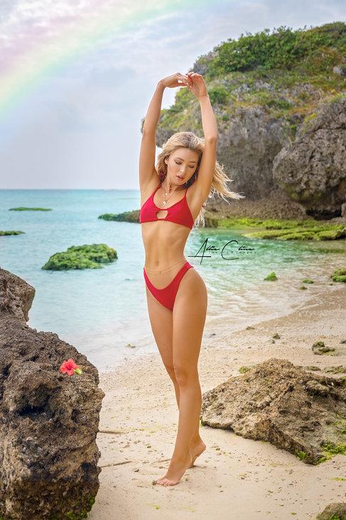 model in red bikini at beach with a rainbow