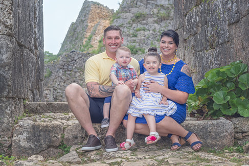 Happy family in blue and yellow posed sitting on step