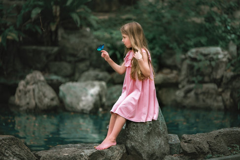 girl in pink dress at pond holding a butterfly