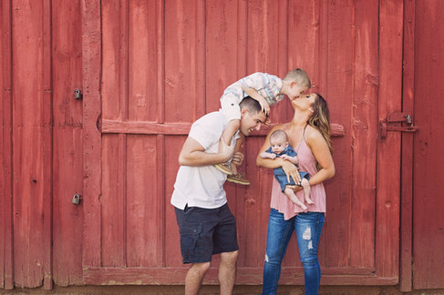 family portrait in front of rustic red barn