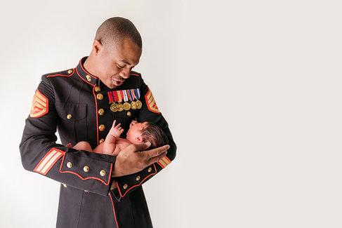 marine in dress blues hushing crying baby white backdrop
