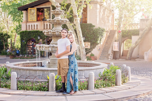 couple embracing in sunshine near water fountain