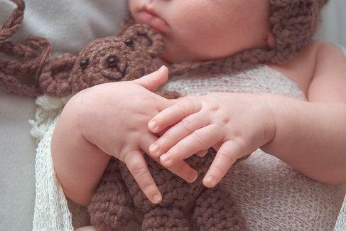 newborn hands holding brown teddy bear