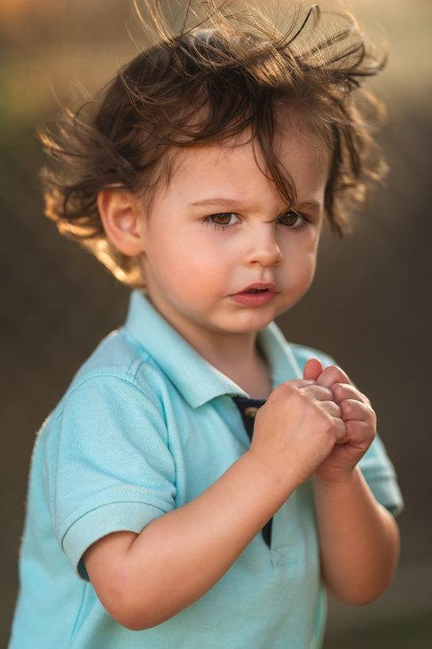 Backlit golen hour toddler boy in blue shirt