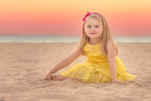 girl in yellow dress sitting on beach at sunset