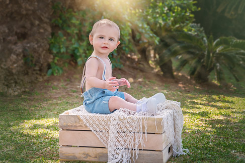 baby sitting on a box in spring fine art portrait