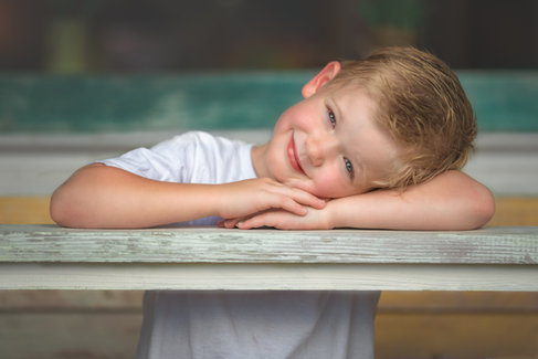 blonde boy resting head on arms pose