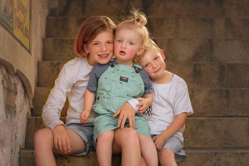 Loving siblings sitting on step cuddling
