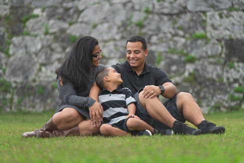 Family sitting in grass smiling at each other