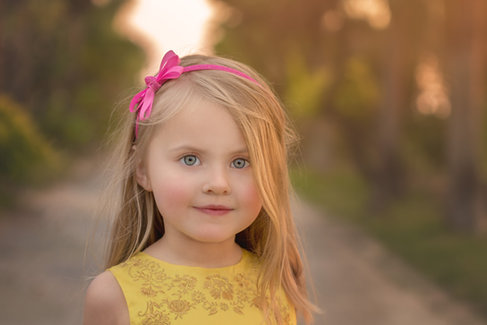 Blonde girl with blue eyes pink bow and yellow dress New Bern fine art photography