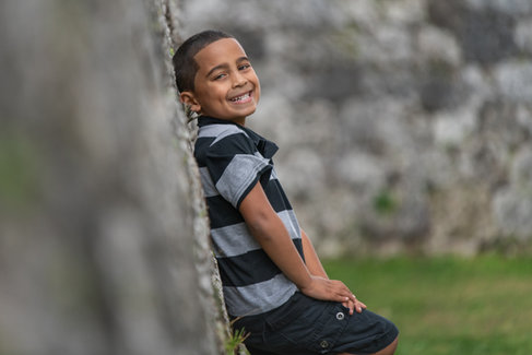 boy in striped shirt leaning against wall smiling