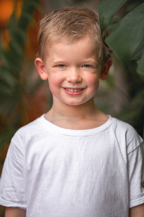 Smiling blonde boy in white shirt boho backdrop