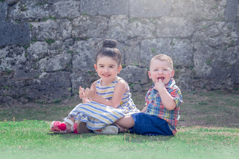 toddler girl and boy siblings sitting in grass