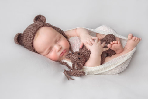newborn baby holding teddy new bern