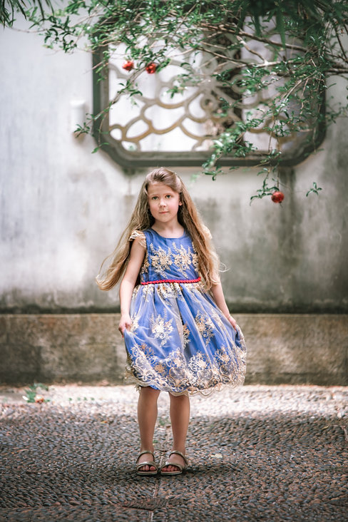 Girl in blue and gold dress with apple on tree