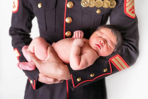 marine in dress blues holding new born baby