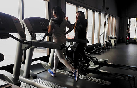 young athlete runs on treadmill while coach cheers her on