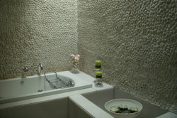 Pebble_stone_cladding_on_the_walls_of_the_bathroom_complementing_the_fixtures_in