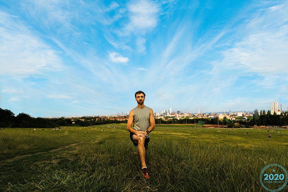 Dr Richard Rees posing for a photo in his running gear on Parliament Hill Fields, London by Jude Wacks for the 2020 Vision Project