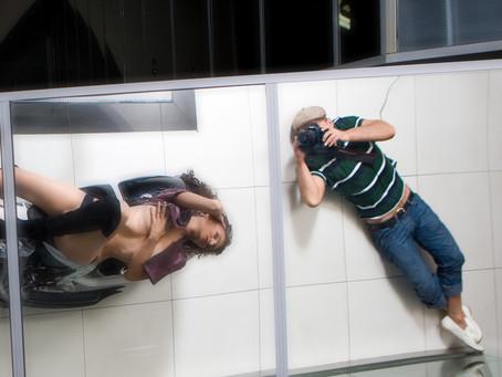 Полуобнаженная модель, лежа на модном байке, позирует фотографу для обложки журнала.