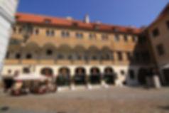 Free Tour Praga Patio Unglet - Unity Tours Praga. En el patio de la iglesia del Týn, junto a la plaza de Ciudad Vieja, podemos ver multitud de terrazas de los bares anexos, además de alguna que otra tienda de souvenirs. Pero no siempre tuvo este patio la misma función. Antiguamente era conocido por ser el lugar de reunión de los mercaderes turcos, que vendían sus mercancías en tenderetes, además de reunirse en sus tabernas. El patio (conocido también como patio de Ungelt) funcionaba además como la aduana real.  La leyenda cuenta que uno de los taberneros de este patio tenía una hija bellísima, inalcanzable para cualquier pretendiente. Decían de ella que tenía un corazón de piedra. Esto cambió cierto día que llegaron unos mercaderes turcos a comerciar en el patio de Ungelt. Uno de ellos era un joven del cual la bella muchacha quedó prendada, y entre ellos surgió una secreta historia de amor. Pero pasado el tiempo de mercaderías, los turcos tuvieron que dejar la ciudad y seguir su camino