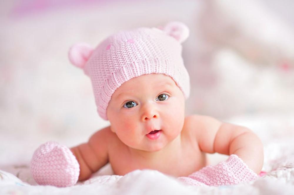 Изненадено бебе ои носи розова плетена капа и ракавици