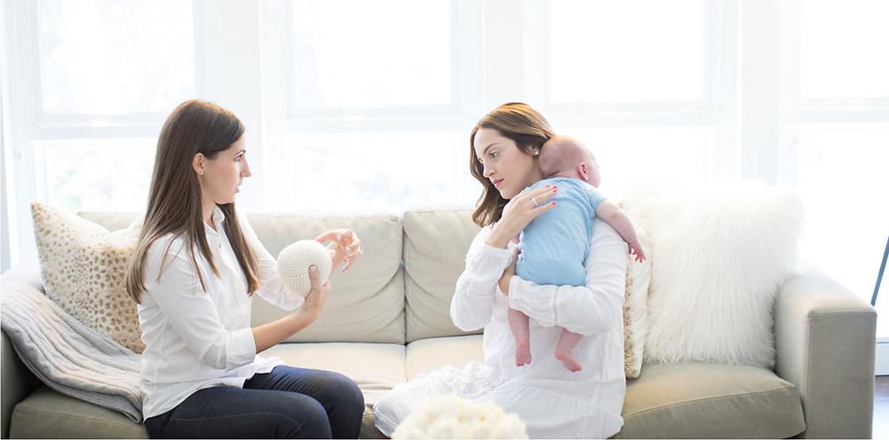 Мајката го држи бебето додека разговара со дадилката