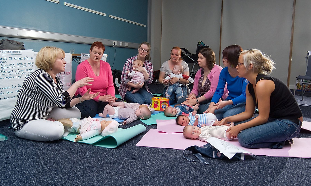 Советник за доење држи работилница за доење со шест мајки и нивните бебиња