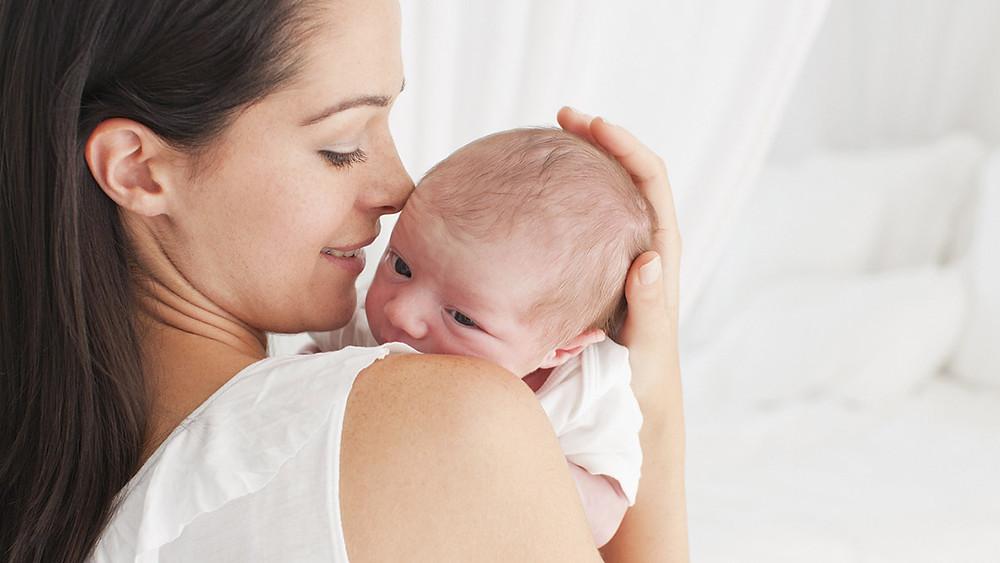 Новороденче во рацете на својата мајка која нежно го гали по главата