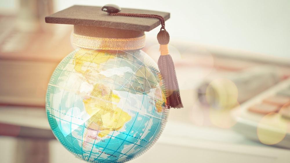 Глобус на светот над кој стои капа за дипломирање