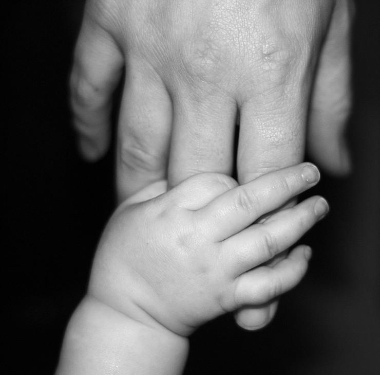 Детска рака држи рака на возрасен