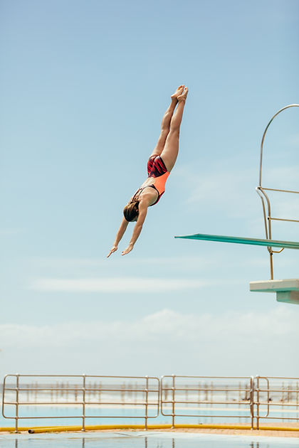 Woman diving into the pool from spring b
