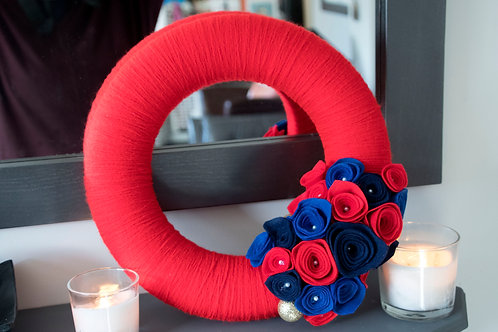 Red Wool Wreath with Red, and Blue Flowers, and Gold Accents.