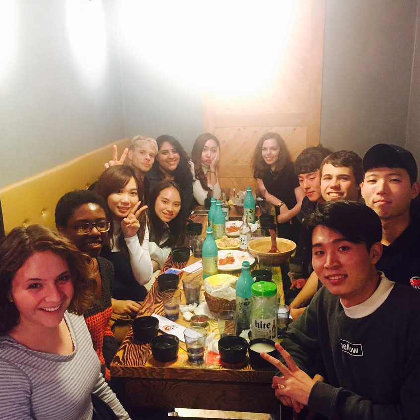 This is a typical weekend night. Many people crowded around a table, sharing snacks and bottles of Soju, as well as bowls of Makgeolli (served cold, almost like a Slushee, ladled out to small wooden bowls to drink from).