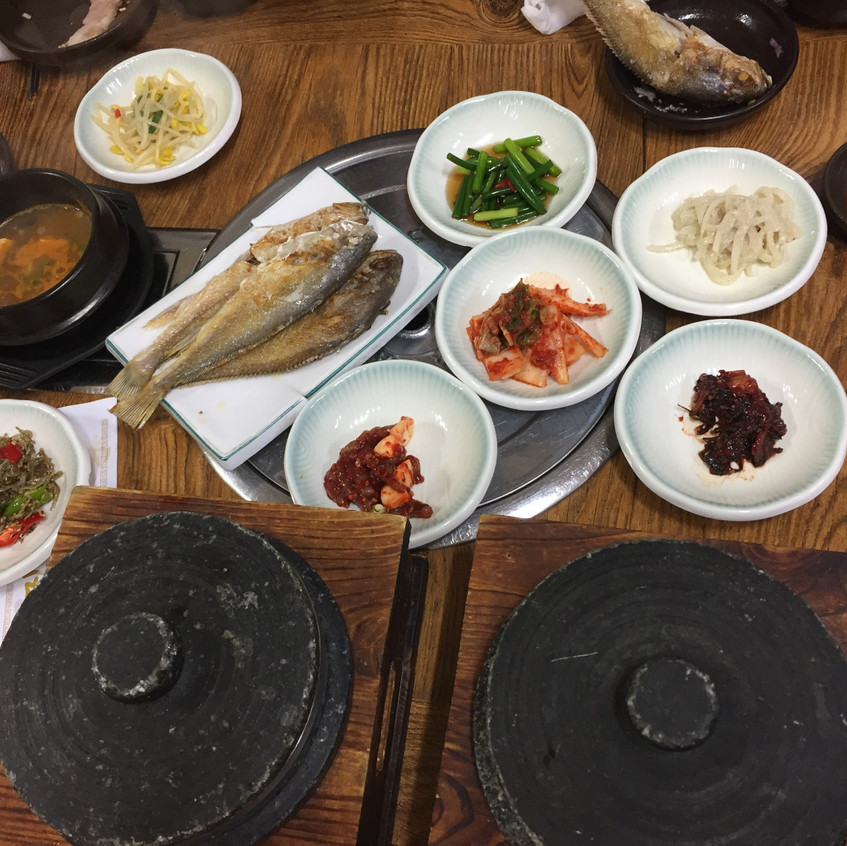 A very traditional meal including soup in stone bowls that is served still boiling, kimchi (a fermented cabbage side dish), pickled sprouts, gently fried whole fish, fermented black beans, a spicy peanut-based spread and chopped greens.