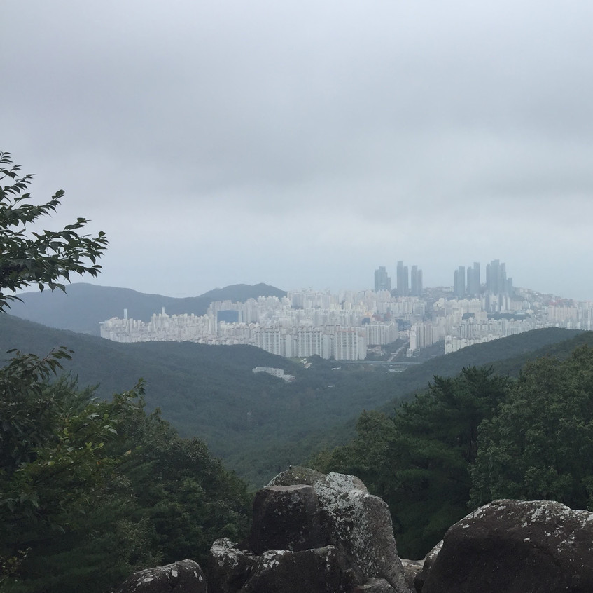 The large coastal city of Busan is tucked in between mountains, clearly illustrating why traditions tell of the Korean  people's strength and power flowing down from the mountains and their ancestors into the cities.