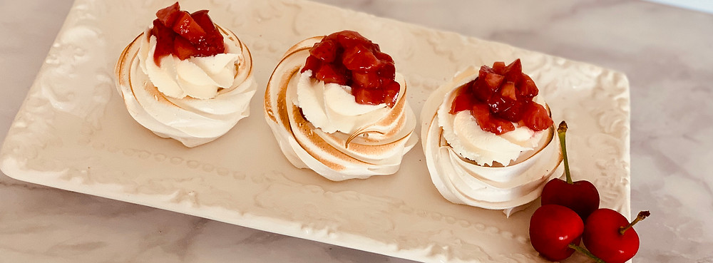mini pavlovas with cherries and strawberries