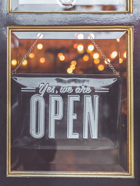 Open vintage sign broad through the glass of store window. Asia_edited.jpg