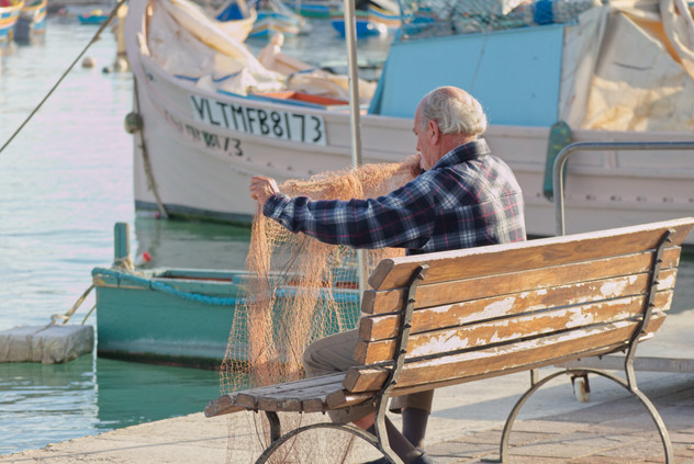 Fisherman repairning his net, Marsaxlokk, Malta
